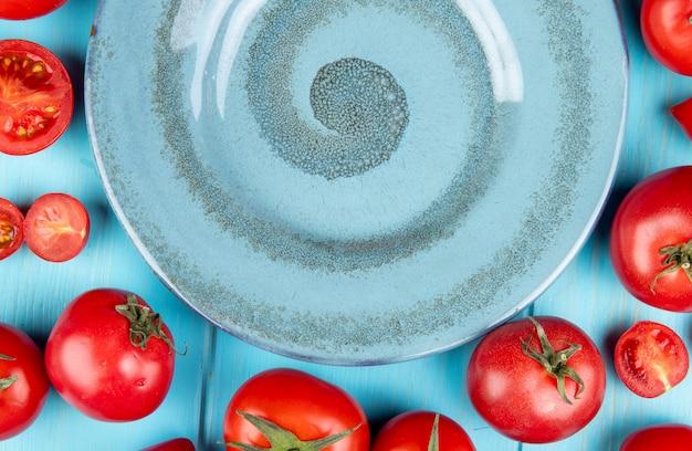 Vista del primo piano dei pomodori tagliati e interi intorno al piatto su fondo blu