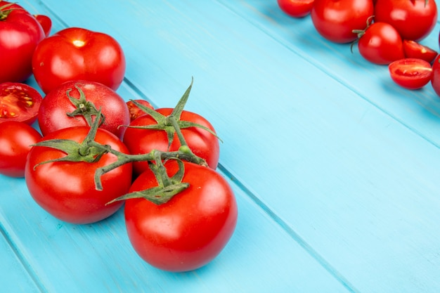 Vista del primo piano dei pomodori tagliati e interi su fondo blu