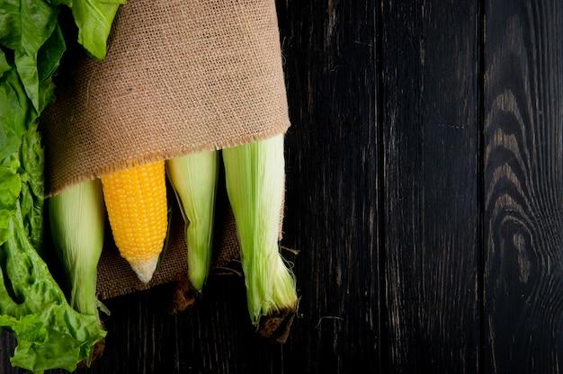 Vista del primo piano dei semi cotti e crudi in sacco con lattuga e spinaci su fondo nero con lo spazio della copia