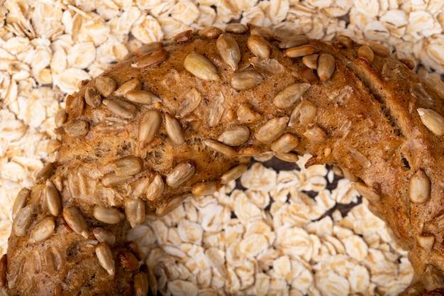 Vista del primo piano dei semi di girasole sul bagel sul fondo dell'avena