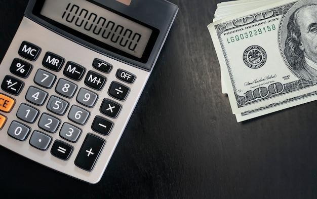 Vista del primo piano del calcolatore e delle banconote sulla tavola di legno scura.