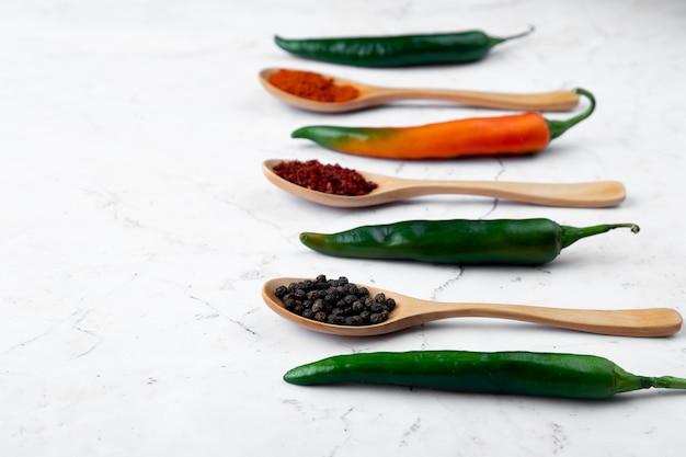 Vista del primo piano del cucchiaio pieno della spezia del pepe con pepe e altre spezie su fondo bianco con lo spazio della copia