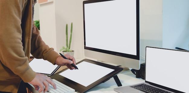 Vista del primo piano del grafico maschio professionale che lavora al suo pro getto con la compressa digitale dello schermo in bianco
