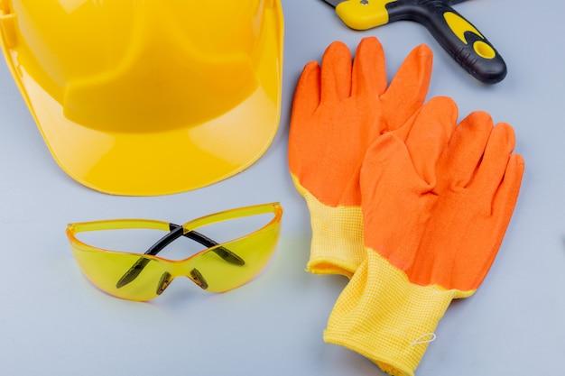 Vista del primo piano del modello dall'insieme degli strumenti della costruzione come coltello e guanti del mastice del casco di sicurezza degli occhiali di protezione su fondo grigio