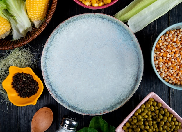 Vista del primo piano del piatto vuoto con le coperture e la seta del cereale dei semi del cereale del pisello del pepe nero su fondo nero