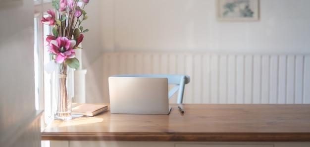 Vista del primo piano del posto di lavoro comodo con derisione sul computer portatile, articoli per ufficio e vaso di fiori rosa sulla tavola di legno