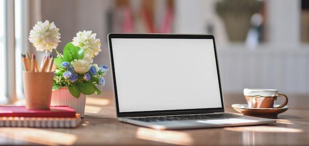 Vista del primo piano del posto di lavoro comodo con derisione sul computer portatile e sugli articoli per ufficio sulla tavola di legno
