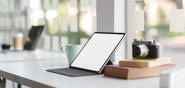 Vista del primo piano del posto di lavoro comodo con tablet mock-up e articoli per ufficio
