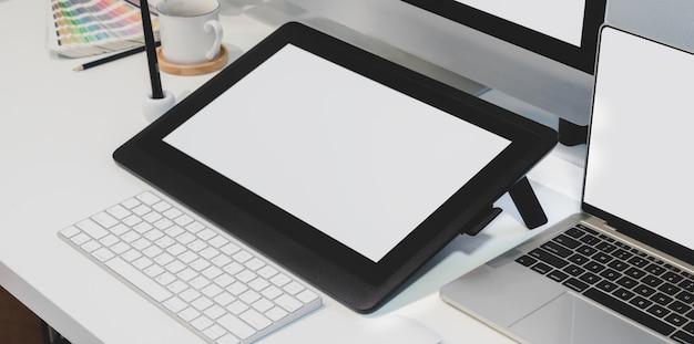 Vista del primo piano del posto di lavoro del progettista con la compressa digitale dello schermo in bianco con il desktop computer