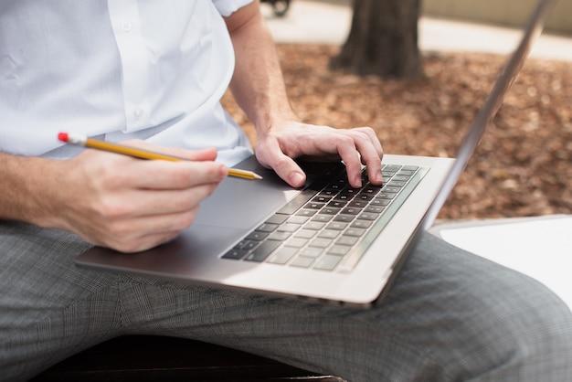 Vista del primo piano del ragazzo che tiene il suo computer portatile e una matita