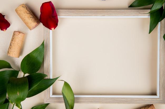 Vista del primo piano del telaio con i sugheri su bianco decorato con le foglie ed i petali del fiore con lo spazio della copia