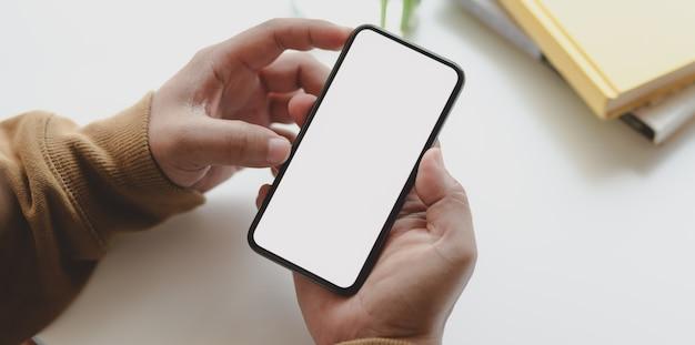 Vista del primo piano dell'uomo che tiene lo smartphone dello schermo in bianco mentre lavorando al suo progetto
