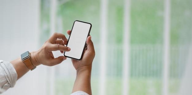 Vista del primo piano dell'uomo che tiene lo smartphone dello schermo in bianco