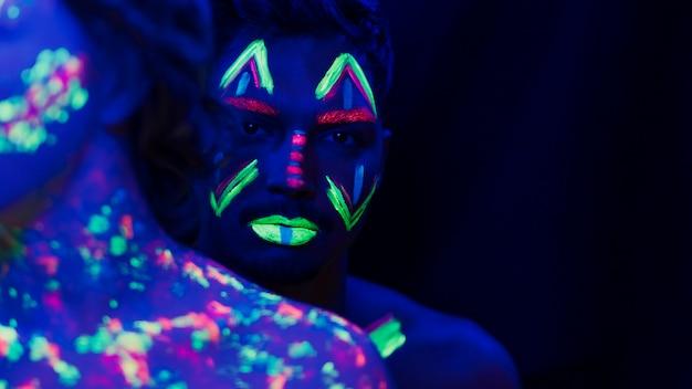 Vista del primo piano dell'uomo con trucco fluorescente variopinto