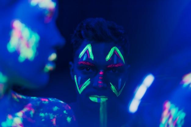 Vista del primo piano dell'uomo con trucco fluorescente