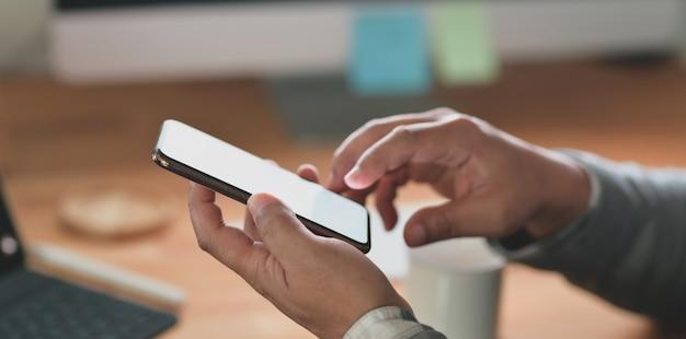 Vista del primo piano dell'uomo d'affari professionale che esamina il suo smartphone dello schermo in bianco