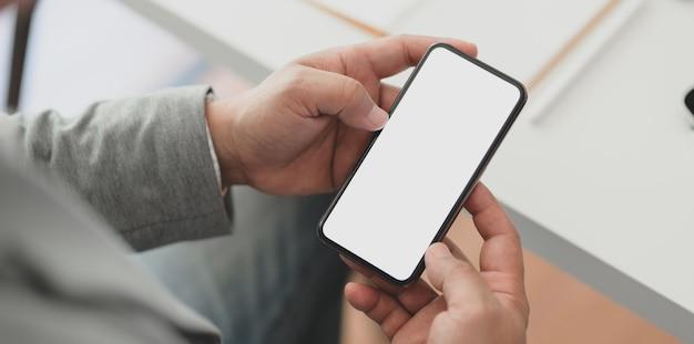 Vista del primo piano dell'uomo d'affari professionale che tiene lo smartphone dello schermo in bianco