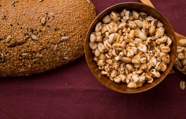 Vista del primo piano della ciotola in pieno di semi e di pannocchia seminata sul fondo di borgogna con lo spazio della copia