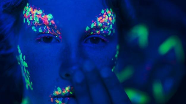 Vista del primo piano della donna con trucco fluorescente variopinto