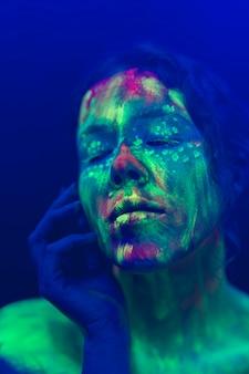 Vista del primo piano della donna con trucco fluorescente