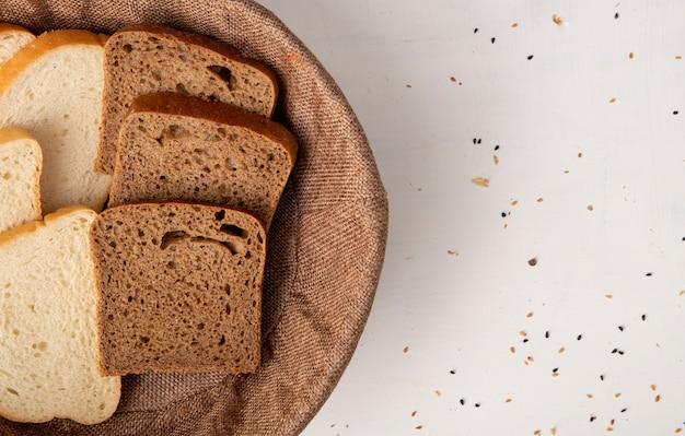 Vista del primo piano della merce nel carrello delle fette del pane di segale e bianco dalla parte di sinistra e fondo bianco con lo spazio della copia