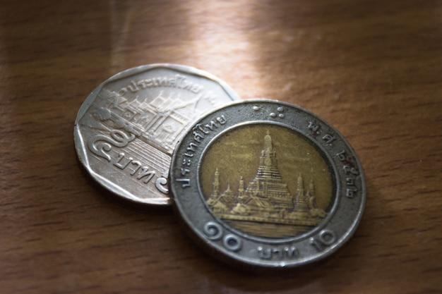 Vista del primo piano della moneta tailandese su terra di legno