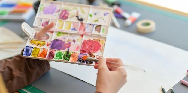 Vista del primo piano della pittura professionale dell'artista femminile sul suo progetto con i colori di acqua