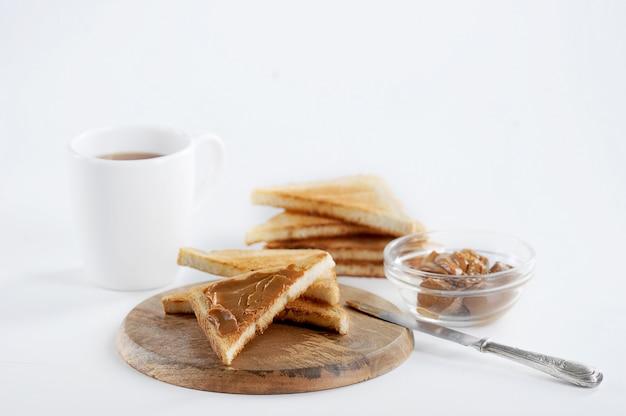 Vista del primo piano della prima colazione saporita del pane tostato con inceppamento del latte condensato