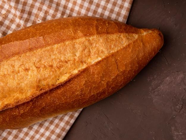 Vista del primo piano delle baguette sul panno del plaid su fondo marrone rossiccio con lo spazio della copia
