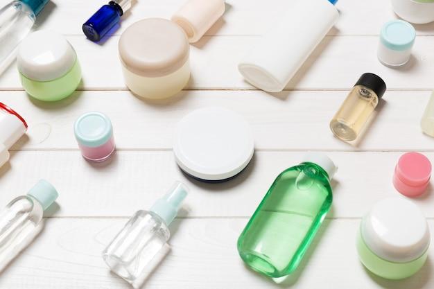 Vista del primo piano delle bottiglie, dei barattoli, dei contenitori e degli spruzzi cosmetici su fondo di legno bianco. concetto di bellezza con spazio di copia