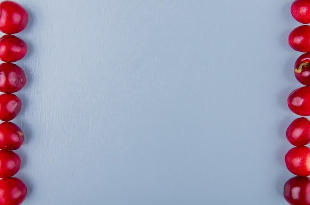 Vista del primo piano delle ciliege rosse dai lati destro e sinistro sulla superficie blu con lo spazio della copia