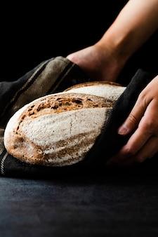 Vista del primo piano delle mani che tengono pane