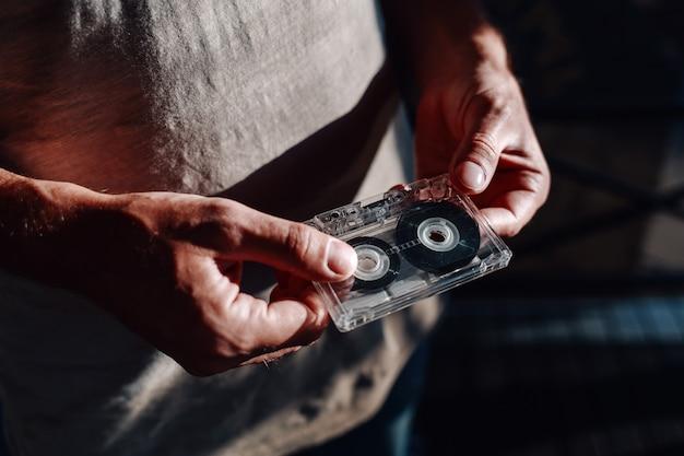Vista del primo piano delle mani dell'uomo che tengono audiotape