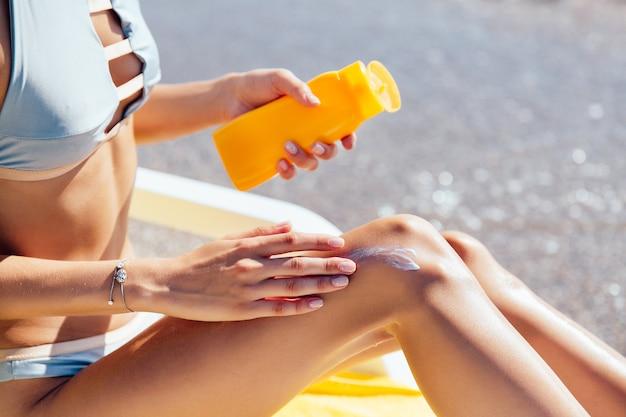 Vista del primo piano delle mani femminili che applicano protezione solare sulla sua gamba, sulla spiaggia. prendere il sole.