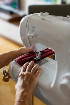 Vista del primo piano delle maschere di protezione del panno di cucito di una persona senior