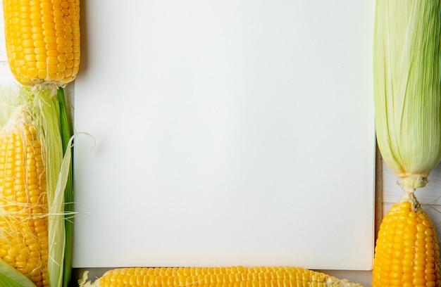 Vista del primo piano delle pannocchie di granturco e del blocco note con lo spazio della copia