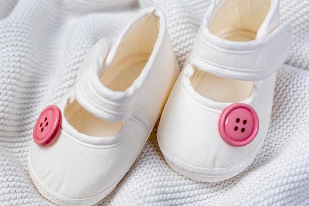 Vista del primo piano delle scarpe sveglie della bambina sulla coperta