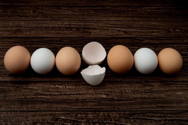 Vista del primo piano delle uova e del guscio d'uovo su fondo di legno