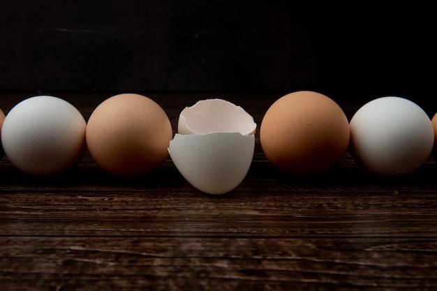 Vista del primo piano delle uova e del guscio d'uovo su superficie di legno e su fondo nero