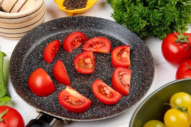 Vista del primo piano delle verdure come coriandolo dei semi del pepe nero del pomodoro con le fette del pomodoro in padella sulla tavola di legno