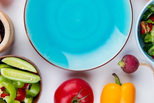 Vista del primo piano delle verdure come pomodoro del pepe del ravanello con insalata di verdure e piatto vuoto sulla tavola bianca