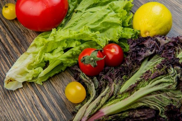 Vista del primo piano delle verdure come pomodoro della lattuga al basilico con il limone sulla tavola di legno