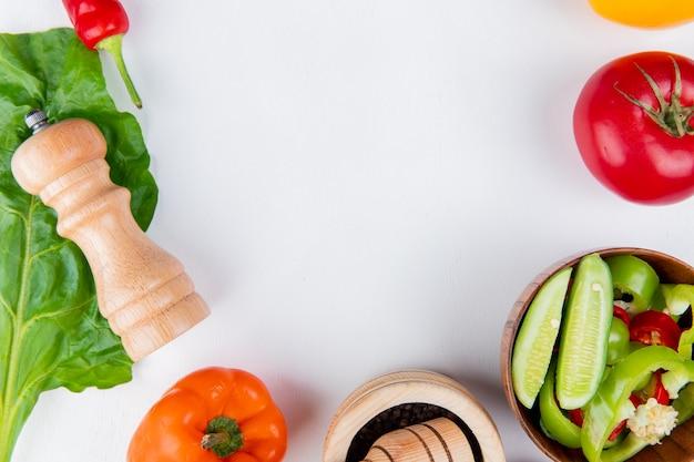 Vista del primo piano delle verdure come pomodoro di pepe con il sale di insalata di verdure e lasciare sulla tavola bianca con lo spazio della copia