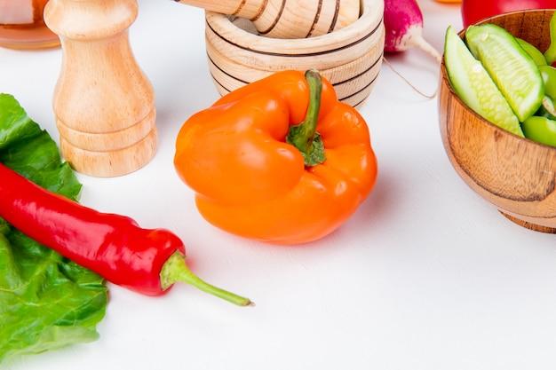 Vista del primo piano delle verdure come ravanello del pomodoro del pepe con pepe nero del sale di insalata di verdure e permesso sulla tavola bianca