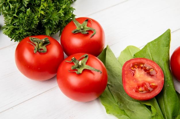 Vista del primo piano delle verdure come spinaci del pomodoro di coriandolo sulla tavola di legno