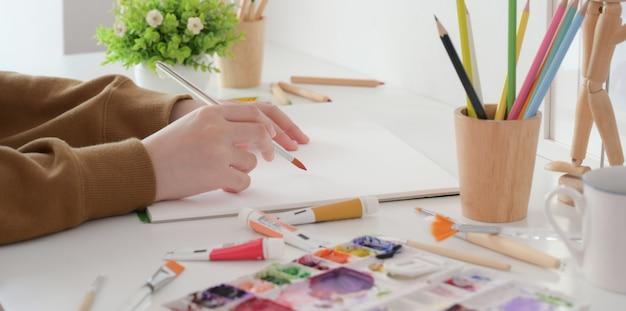 Vista del primo piano di giovane artista femminile che dipinge il suo progetto con colore di acqua con la spazzola di pittura