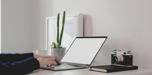 Vista del primo piano di giovane femmina che lavora al suo progetto mentre scrivendo sul computer portatile dello schermo in bianco