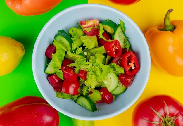 Vista del primo piano di insalata di verdure in ciotola con il limone del pomodoro del pepe su fondo verde e giallo