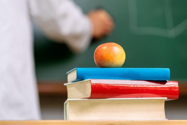 Vista del primo piano, di una scrivania dell'insegnante con una pila di libri e una mela rossa davanti ad una lavagna.