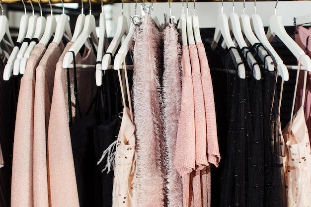 Vista del primo piano di vari vestiti alla moda che appendono sui ganci in boutique. abiti
